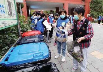 ??  ?? 志愿者指导居民正确投放生活垃圾