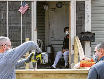 ?? Godofredo A. Vásquez / Staff photographer ?? Adele O'Neal, center, watches volunteers build a new ramp Monday for her house in Acres Homes.