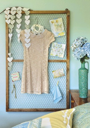 """??  ?? THIS OLD CHICKEN-WIRE frame came off one of Sara's barn windows and is a great way to organize and display mementoes. """"I hung the dress here because it was something special that I wore out on a weekend away with my husband,"""" Sara says. """"And I made the paper heart garland because I've always adored hearts and enjoy making cute and affordable projects."""""""