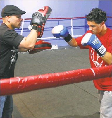 ?? Peter Hvizdak / Hearst Connecticut Media ?? In this 2009 file photo, boxer Luis Rosa Jr., right, is in the ring with his father and trainer Luis Rosa at the Boxing in Faith Gym The younger Rosa was killed in an automobile accident in January and his friend, Charles Foster, will honor him when he...