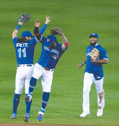 ?? GREGORY FISHER / USA TODAY SPORTS FILES ?? Toronto Blue Jays infielders Bo Bichette and Jonathan Villar, with outfielder Teoscar Hernandez, celebrate a victory over the New York Yankees Sept. 24 at Buffalo's Sahlen Field — clinching the team's first playoff spot since 2016.