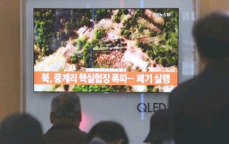 ?? AHN YOUNG-JOON/ASSOCIATED PRESS ?? People watch a satellite image of the Punggye-ri nuclear testing site on a TV screen at the Seoul Railway Station. North Korea carried out what it said is the demolition of its nuclear test site Thursday, setting off a series of explosions over several...