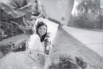 ?? Photos by Jim Mahoney/Staff Photographer ?? A memorial to Lauren Huddleston — including a Texas Longhorns flag, flowers and a photograph — is attached to Katy Trail marker 107, the spot at which the 28-year-old tax consultant was hit by a bicyclist in September while jogging.