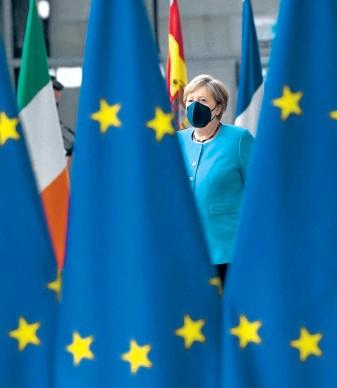 """?? ?? 16 Jahre lang ein gewohntes Bild: Angela Merkel bei ihrer Ankunft im """"Flaggenwald""""von Brüssel – zuletzt freilich wegen der Pandemie mit Maske."""