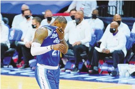 ?? MATT SLOCUM/ASSOCIATED PRESS ?? The Lakers' LeBron James wipes his face after missing back-to-back free throws late in LA's one-point loss to the 76ers in Philadelph­ia on Wednesday night.