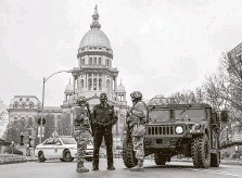 ?? Justin L. Fowler / Associated Press ?? Members of the Illinois National Guard and the Capitol Police are posted at a road closure Sunday near the Illinois State Capitol.