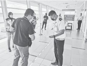 ??  ?? JALANKAN TUGAS: Pegawai dan anggota polis memeriksa dokumen individu yang memasuki Bintulu melalui penerbangan domestik di Lapangan Terbang Bintulu.