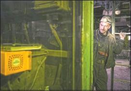 ??  ?? A Bosnian coal miner checks equipment in an underground tunnel.