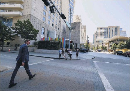 ?? Photos by Smiley N. Pool/staff Photographer ?? Lothar Estein, CEO of Victory Park's largest owner, Estein USA, crossed Olive Street at Victory Park Lane after a ceremony marking the completion of the new retail street at Victory Park on Tuesday.