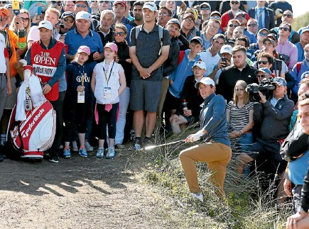 ?? PHOTO: REUTERS ?? Dozens of fans, and caddie JP Fitzgerald, left, get a close-up look at world No 4 Rory McIlroy as he plays from the rough on the eighth hole.