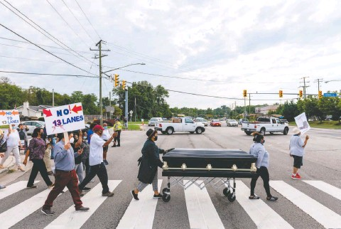?? ERIC LEE FOR THE WASHINGTON POST ?? Residents move a casket across Richmond Highway on Thursday to demonstrate the possible traffic-related deaths from its expansion in Gum Springs, one of the oldest Black suburban neighborhoods in the country. The community last called upon the casket in 1967.
