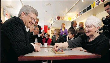 ?? Chris Wattie, Reuters ?? conservative leader stephen Harper plays cribbage with susan collins during a campaign stop at a cultural centre in toronto wednesday. on wednesday, Harper offered an apology to a student who was kicked out of a rally earlier this week.