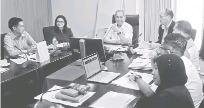??  ?? MUTARKA PENANGGUL RAYAT : Wan Junaidi(duduk tiga kiba) ngulu aum begulai enggau sekeda ejensi perintah ke bisi kaul enggau projek di kandang Parlimen Santubong di Kuching ensanus.