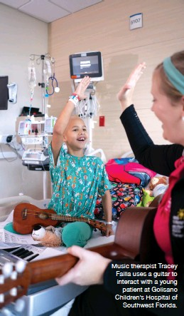 ??  ?? Music therapist Tracey Failla uses a guitar to interact with a young patient at Golisano Children's Hospital of Southwest Florida.