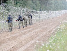 ?? ?? Polish soldiers build a fence on the border between Poland and Belarus. Thousands of migrants have crossed or tried to cross into the European Union from Belarus in recent months. — Reuters