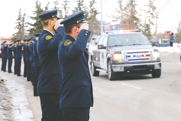 ?? Daren Makowichu k ?? Calgary police and first responders from all over the province held a parade around Falconridge on Monday as citizens continued to lay flowers at the location where Sgt. Andrew Harnett was killed Thursday night after he was struck by a fleeing vehicle at a traffic stop in Calgary.