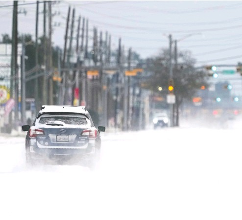 ?? DAVID J. PHILLIP / The ASSOCIATED PRESS ?? Vehicles drive on snow- and sleet-covered roads Monday in Spring, Texas, as a winter storm prompted a power emergency and the shutdown of the largest oil refinery in North America in Port Arthur.