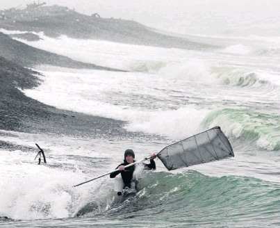 ?? PHOTOS: STEPHEN JAQUIERY ?? Chancing his luck . . . A whitebaiter fishes in the breaking waves on the north side of the Waitaki River mouth yesterday.