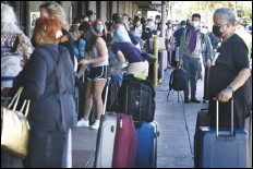 ?? ASSOCIATED PRESS ?? A long line of travelers waits Thursday to pass through a state agriculture inspection at the Kahului Airport on the Hawaiian island of Maui. Maui has become so overrun with tourists in recent months that its mayor is taking the unusual step of pleading with airlines to fly in fewer people.