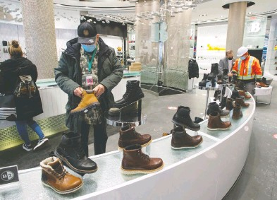 ?? RYAN REMIORZ / THE CANADIAN PRESS ?? Customers shop for boots as an easing of COVID-19 restrictions allow non-essential stores to reopen Monday in Montreal. Health officials are warning Canadians of the potential for increased contagiousness of the COVID variants.