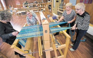 ?? MATHEW MCCARTHY PHOTOS WATERLOO REGION RECORD ?? Judy Ginsler, left, Susan Neff, Helene Bindsei and Barb Dares feed yarn through a loom at the Kitchener-Waterloo Weavers and Spinners Guild.