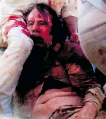 ?? REUTERS TV ?? Moammar Gadhafi, covered in blood, is held on the ground in Sirte in this still image taken from video Oct. 20, 2011. He died shortly after. Some believe his killing was nothing more than an execution.
