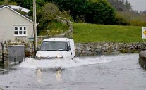 ?? Picture: Paul Mealey ?? A car tries to make the school run on a flooded road at the Quay in Westport, Co Mayo.