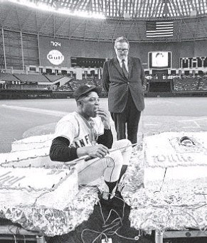 ?? AP ?? Willie Mays licks fingers in center field of Astrodome after cutting birthday cake given to him by Astros owner Roy Hofheinz, standing, in celebration of 37th birthday in 1968.