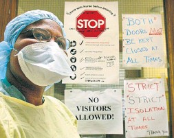 """?? KEVIN FRAYER THE CANADIAN PRESS FILE PHOTO ?? A nurse wears protective gear at Sunnybrook hospital while standing outside the door of a quarantined patient during the 2003 SARS crisis. """"Experiences like SARS should have alerted us how to do this,"""" says Dr. Charles Dela Cruz of the Yale School of Medicine. """"It's unfortunate that we haven't really learned much."""""""