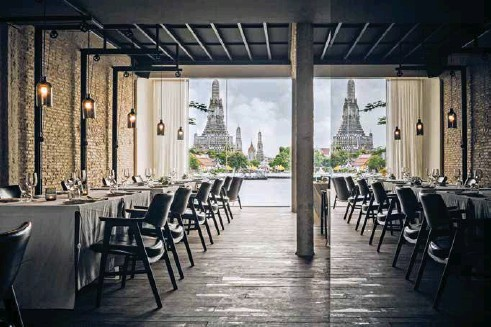 ??  ?? Above: A mirrored wall within the restaurant at Sala Rattanakosin reflects the Temple of Dawn across the Chao Phraya River. Photo by Wison Tungthunya. Opposite: Chaiamnuay and Chaktranon outside their Sathorn studio in Bangkok.