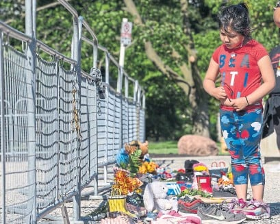 ?? RICK MADONIK PHOTOS TORONTO STAR ?? Karlee Jackson, 5, looks at shoes left at a small memorial at Queen's Park honouring the recently discovered mass grave at the Kamloops Residential School in British Columbia. She left shoes and a teddy bear after visiting with her mother on Sunday.