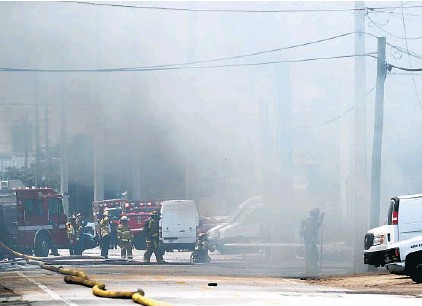 ?? AMY BETH BENNETT/SOUTH FLORIDA SUN SENTINEL ?? Firefighte­rs work to extinguish a fire and multiple explosions that gutted Barco Sales & Manufactur­ing, a business that makes custom foam products, inserts and packaging, Wednesday in the Oakland Park warehouse district.