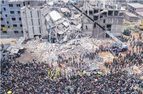 ?? FOTO: IMAGO IMAGES ?? Menschenmenge vor den Ruinen des Rana-Plaza-Komplexes in Sabhar in Bangladesch: Aufgrund von Baumängeln kollabiert das achtgeschossige Gebäude am 24. April 2013, bei der Tragödie sterben 1135 Menschen. Obwohl die Polizei das Gebäude gesperrt hatte, befanden sich zum Zeitpunkt des Unglücks rund 3000 Arbeiterinnen und Arbeiter in dem Komplex, in dem vor allem Textilunternehmen ihren Sitz hatten, die für Kunden auf der ganzen Welt produzierten.