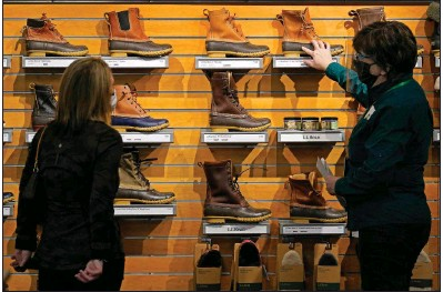 ??  ?? An employee helps a customer shop for Bean Boots last month at the L.L. Bean flagship retail store in Freeport, Maine. Retail sales surged a seasonally adjusted 9.8% in March, the Commerce Department said Thursday.