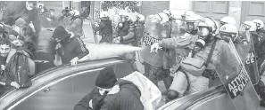 ?? — Gambar AFP ?? HALAU: Polis melepaskan gas pemedih mata untuk meleraikan protes di Athens pada Jumaat lepas.