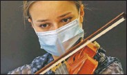 ??  ?? Hildegard De Stefano wears a mask as she plays her violin during a lesson with maestro Luca Braga.