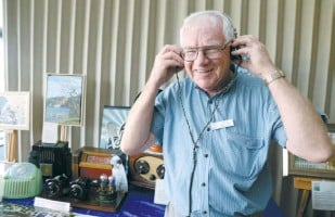 ??  ?? Ron Bowley showcases his extensive radio collection, including 1920s SG Brown headphones.