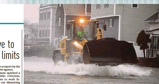 ?? AFP PIC ?? A front-end loader making its way through floodwaters in Quincy, Massachusetts, on Friday.