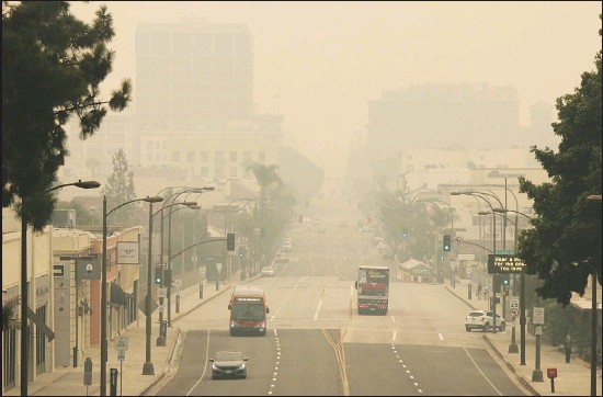 ??  ?? Smoke from wildfires fills the sky over Pasadena, Calif, in this view looking east down Colorado Boulevard in a Sept 12, 2020 file photo. The fires consuming the forests of California and Oregon and darkening the skies over San Francisco and Portland are also damaging an economy already struggling with the coronavirus outbreak. In the communities where they are raging, wildfires are destroying property, running up huge losses for property insurers and putting a strain on economic activity that could linger for a year or more. (AP)