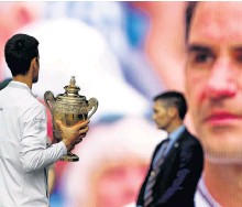 ?? REUTERS ?? Serbia's Novak Djokovic holds the Wimbledon trophy after winning the 2019 final as Switzerland's Roger Federer is on a screen in the background.