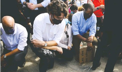 ?? SEAN KILPATRICK / THE CANADIAN PRESS FILES ?? Prime Minister Justin Trudeau takes a knee in June when he participated in an 8 minute, 46 second moment of silence at an anti-racism protest on Parliament Hill.