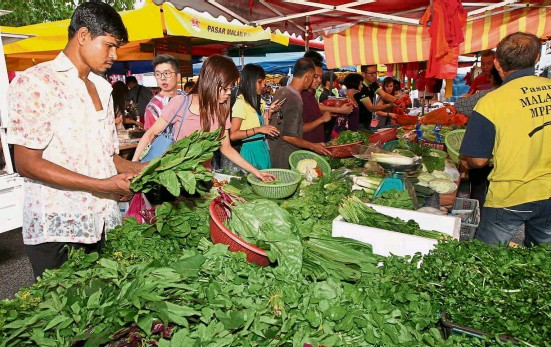 ?? — ART CHEN/ The Star ?? Choosing the best: Customers picking out vegetables at the SS2 night market in Petaling Jaya.