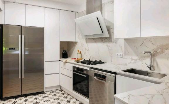 ??  ?? BUENA MEZCLA En la cocina se optó por muebles discretos y de líneas sencillas, de la firma Häcker; electrodomésticos de acero y una encimera Dekton, con suaves vetas en gris.