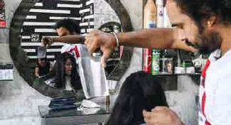 ??  ?? Le coiffeur pakistanais Ali Abbas fait une coupe à la feuille de boucher dans son salon à Lahore , le 8 avril 2021