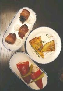 ?? JENNIFER BARDONER PHOTO ?? Tuna-stuffed piquillo peppers, bacon-wrapped dates and potato tortilla, clockwise from bottom.