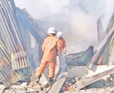 ??  ?? Fire and rescue personnel carrying out an investigation at the fire scene at Kg Kalipuo in Pitas.
