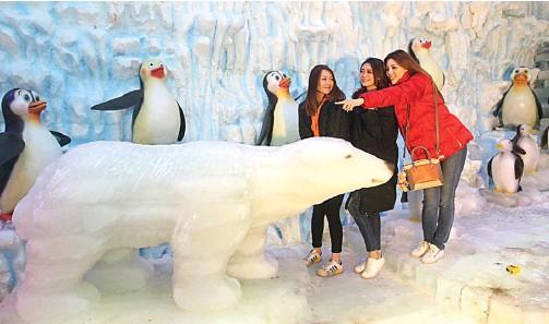 ?? GHOFUUR EKA/JAWA POS ?? SUASANA KUTUB UTARA: Dari kiri, Indo Yasmien Marzy, Jenifer Zefanya, dan Christine Wijaya berkunjung ke istana es yang merupakan wahana baru di Atlantis Land, Kenjeran Park.