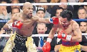 ?? FRED­ERIC J. BROWN/GETTY IMAGES ?? Floyd May­weather Jr., left, eas­ily out­boxed Manny Pac­quiao late Satur­day night. Af­ter the fight, Pac­quiao's team re­vealed that their boxer had fought with a right shoul­der in­jury.