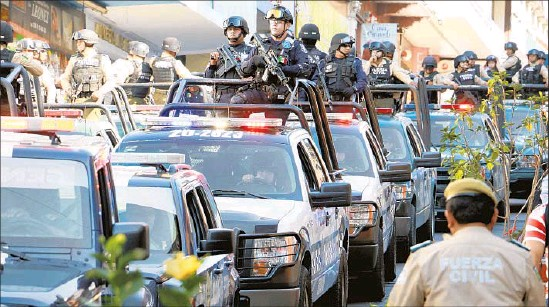 ?? Eduardo Murillo AFP/Getty Images ?? A CONVOY of law enforcement arrives in Jalapa, Veracruz state, to bolster security. A recent rash of killings has raised questions about the U.S. role in the drug war.