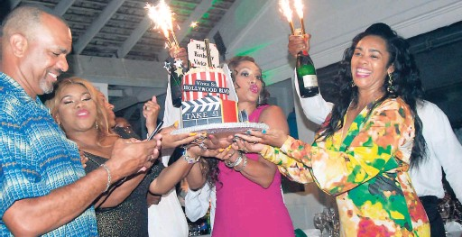 ?? CONTRIBUTED PHOTOS ?? Vivica Fox is assisted to hold up her 51st birthday cake by (from left) Marlon, Khadine 'Miss Kitty' Hylton and Lisa McIntosh, while waiters add some spark with sparkling candles attached to the champagne bottles.